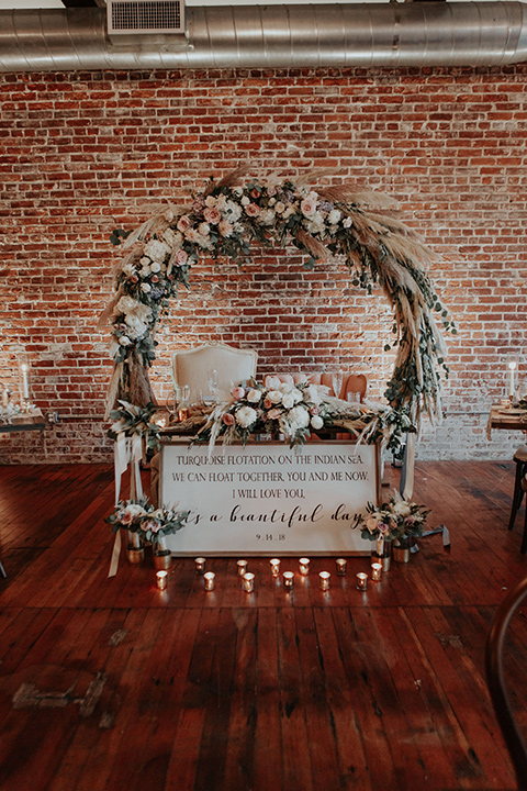 sweetheart table with white linens and a circular arch and pink florals