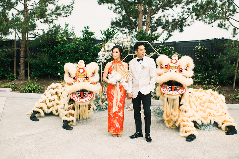 bride and groom in Chinese attire with lion dancers