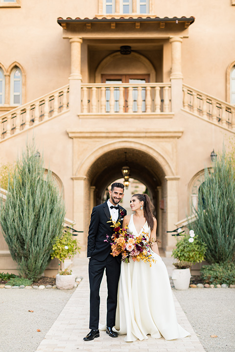 old world wedding at Allegretto Vineyard Resort – bride in a long gown with a cutout back design and the groom in black tuxedo with a black diamond bow tie at ceremony