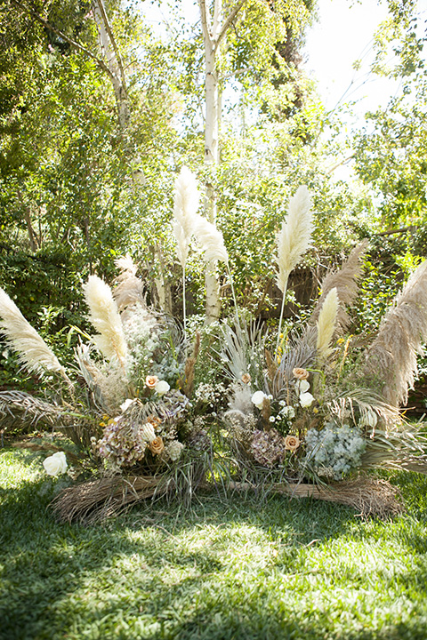 backyard bohemian elopements with the bride in a high neckline gown and the groom in a caramel suit -ceremony arch