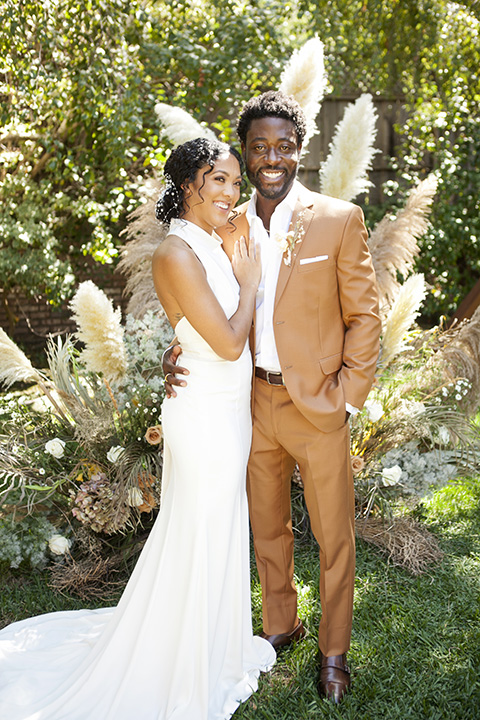 backyard bohemian elopements with the bride in a high neckline gown and the groom in a caramel suit -ceremony