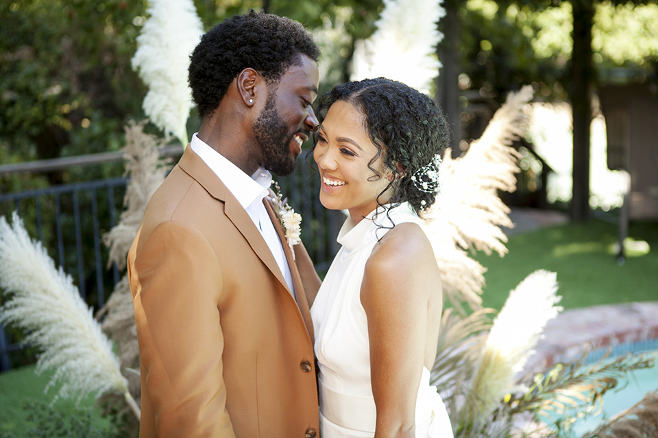 backyard bohemian elopements with the bride in a high neckline gown and the groom in a caramel suit -table