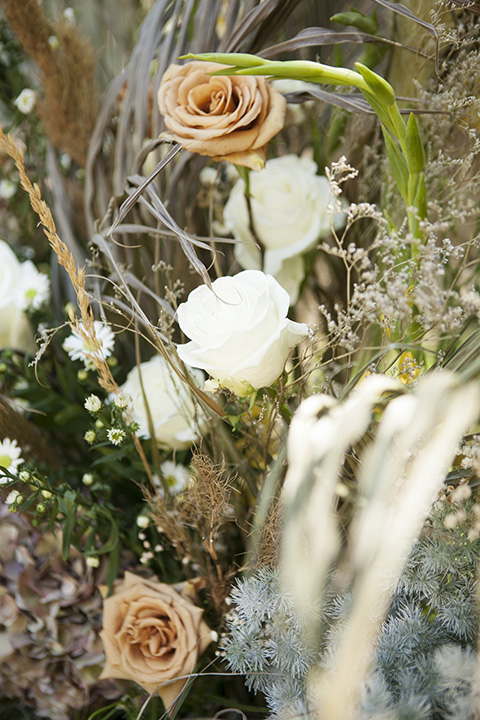 backyard bohemian elopements with the bride in a high neckline gown and the groom in a caramel suit -flowers