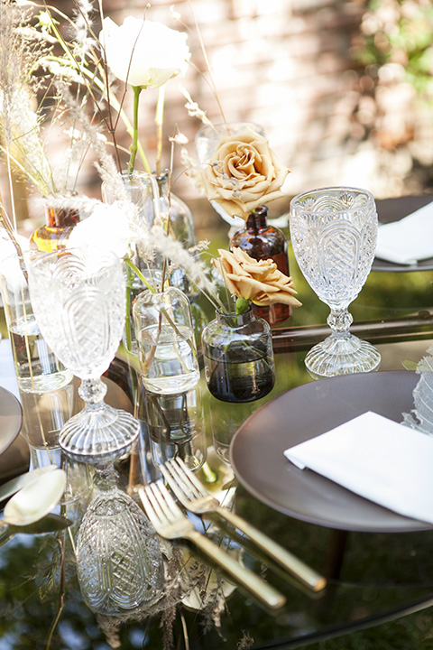 backyard bohemian elopements with the bride in a high neckline gown and the groom in a caramel suit -table decor