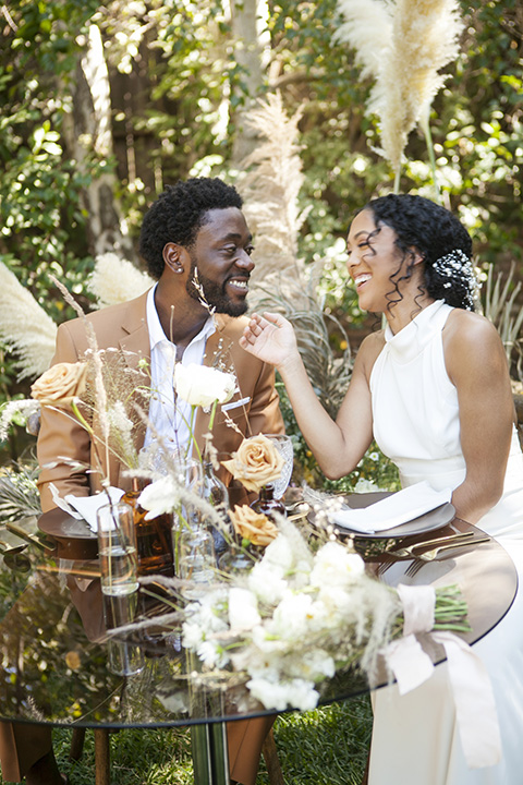 backyard bohemian elopements with the bride in a high neckline gown and the groom in a caramel suit -sitting