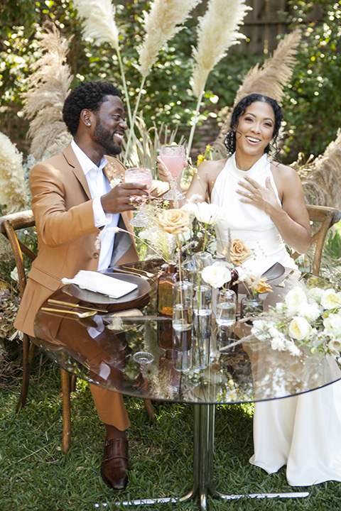 backyard bohemian elopements with the bride in a high neckline gown and the groom in a caramel suit -cheers