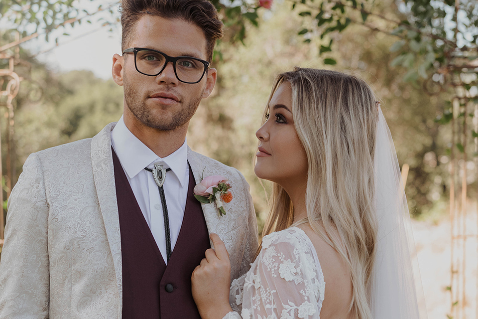 bride in a lace bohemian gown and the groom in an ivory paisley and burgundy ants and a bolo tie