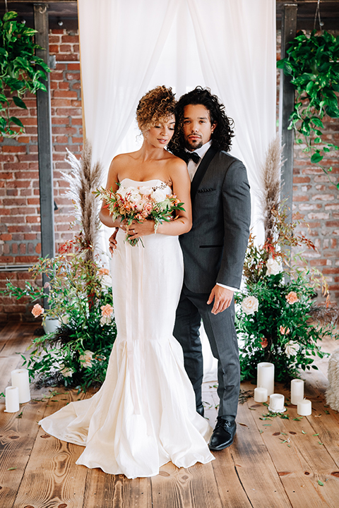 bride in a two-piece gown with her hair in a chic up-do and the groom in a charcoal tuxedo with a black lapel and a black bow tie