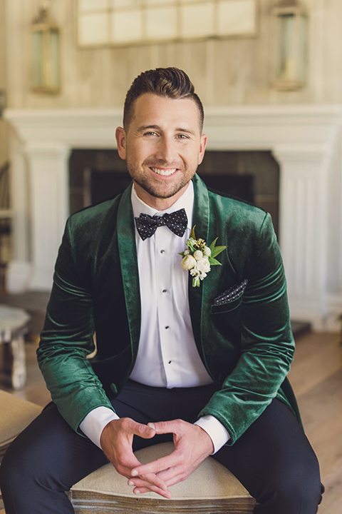 bride in a black lace gown and the groom in a green velvet tuxedo with a black bow tie and shoes