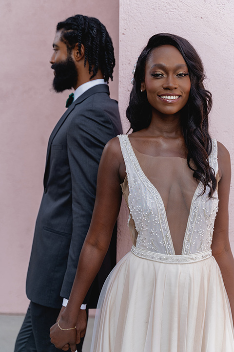 bride in a flowing white gown with a plunging neckline and the groom in a asphalt grey suit
