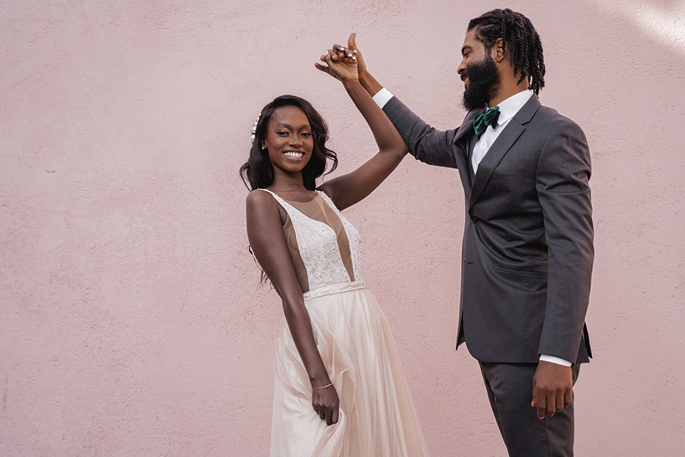 bride in a flowing white gown with a plunging neckline and the groom in an asphalt grey suit