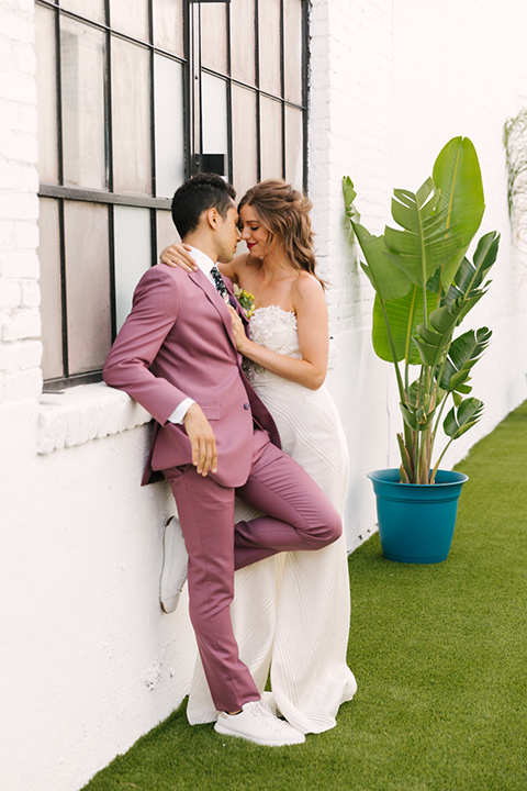 bride in a fashionable white jump suit with a strapless neckline and wide leg and the groom in a rose pink suit with a black floral neck tie