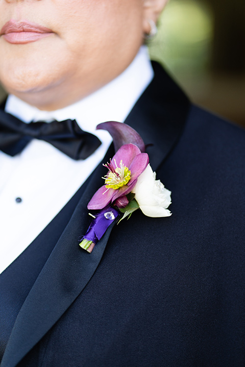 one bride in a black women's tuxedo with a black diamond shaped bow tie