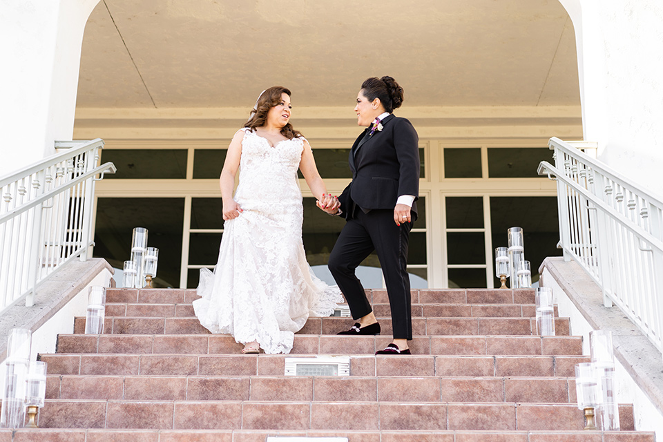 one bride in a black women's tuxedo with a black diamond shaped bow tie and one bride in a white mermaid style gown with a beaded bodice and strapless neckline
