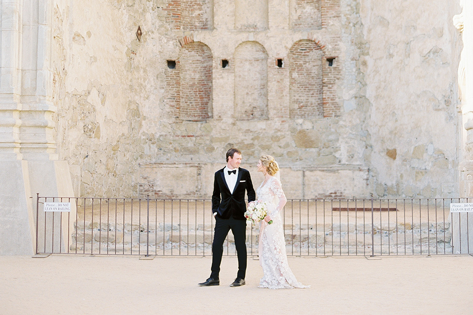bride in a lace white gown with long illusion sleeves and the groom in a black velvet tuxedo