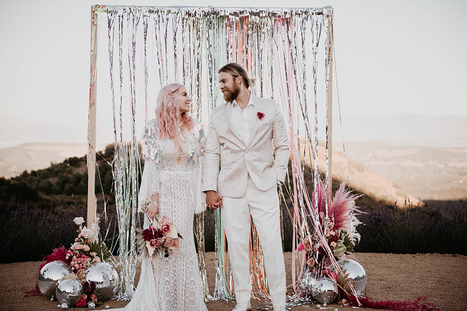 the bride in a fun sequin gown with a faux fur coat and the groom in an ivory paisley tuxedo