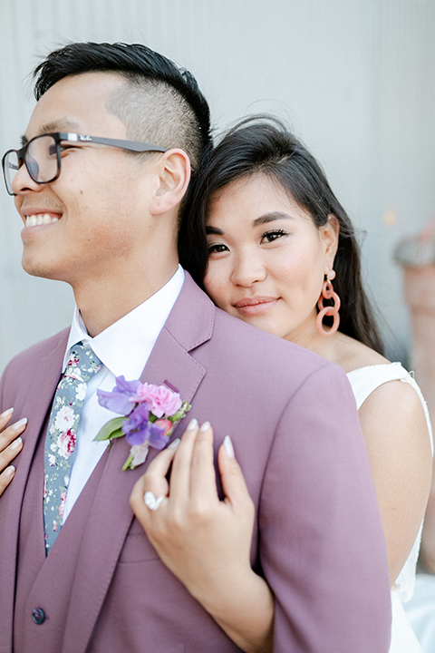 bride in a formfitting gown with a high neck and a long train groom in a rose pink suit and a light blue floral tie
