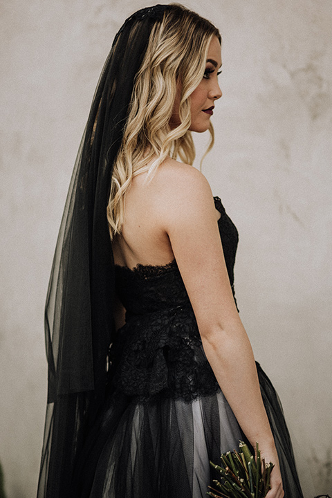 bride in a black and grey gown with a black tulle veil