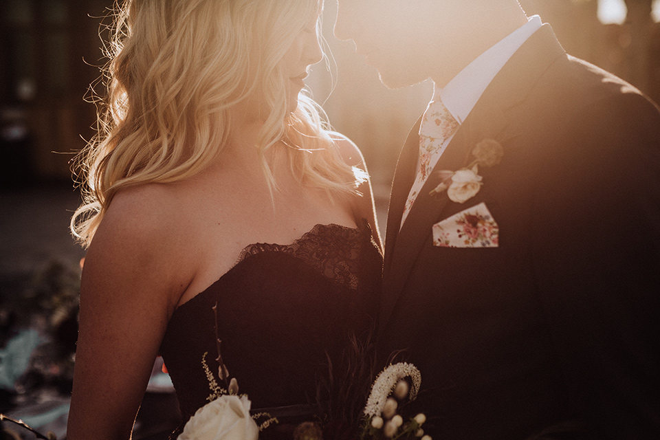 bride in a black and grey gown with a black tulle veil and the groom in a asphalt grey coat with light grey pants and floral white tie