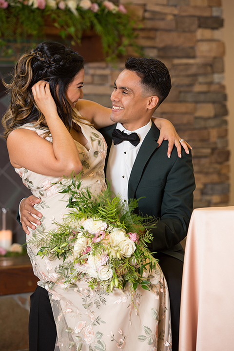 bride in a modern formfitting gown with cap sleeves and a high neck and the groom in a green suit with a floral tie