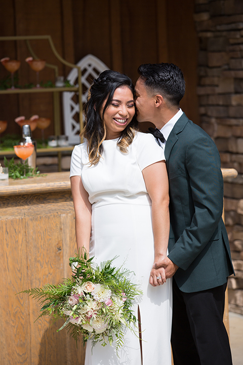 bride in a modern formfitting gown with cap sleeves and a high neck and the groom in a green suit and floral tie