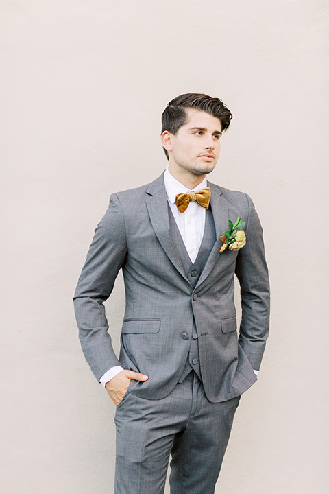 groom in a café brown suit and a gold velvet bow tie