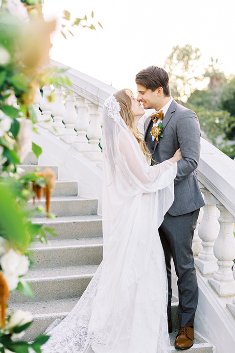 groom in a café brown suit and a gold velvet bow tie bride in a white silk gown with a cape overlay