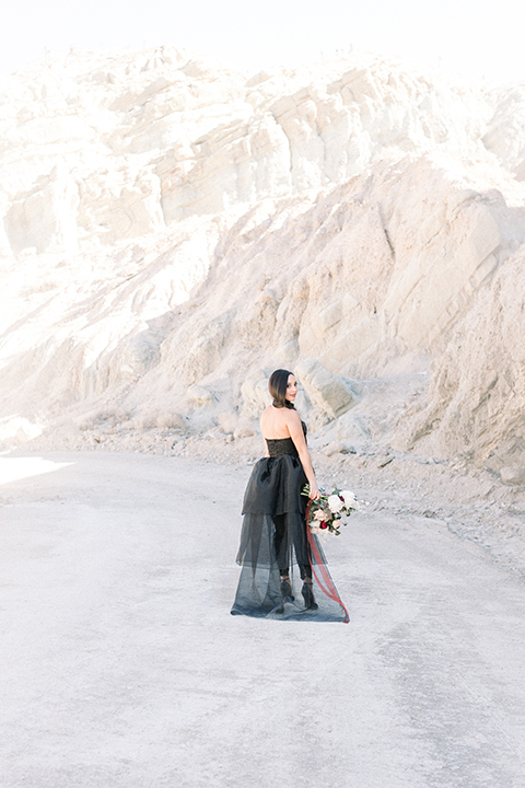 bride in a black jumpsuit with a tulle overlay