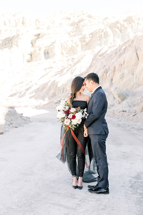 bride in a black jumpsuit with a tulle overlay and the groom in a navy shawl lapel tuxedo with a black long tie