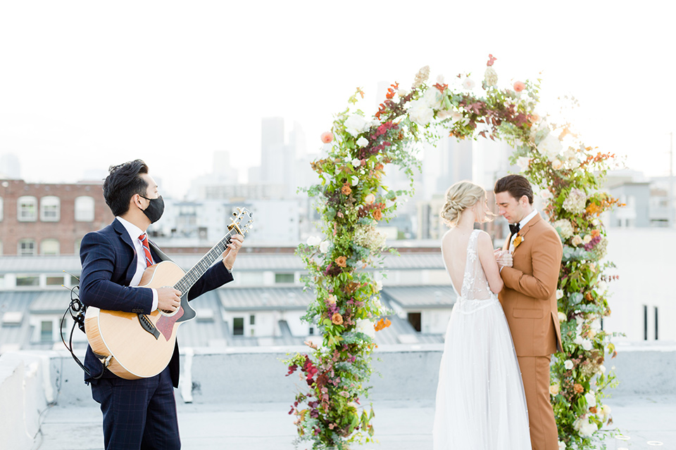 the bride in a white gown with an illusion neckline and hair in a low bun, the groom in a caramel brown suit with a chocolate brown bow tie