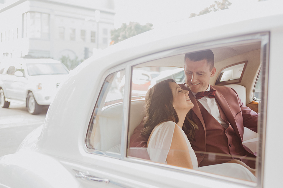 bride in a flowing white gown with flutter sleeves and the groom in a rose-pink suit with a burgundy velvet bow tie
