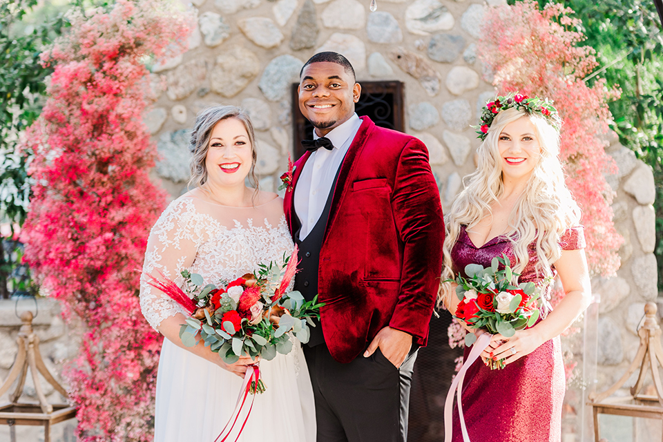 bride in a white and ivory gown with a natural waist and lace long sleeves, the groom in a burgundy velvet tuxedo with a black bow tie, and the bridesmaid in a red velvet long gown and a floral headpiece