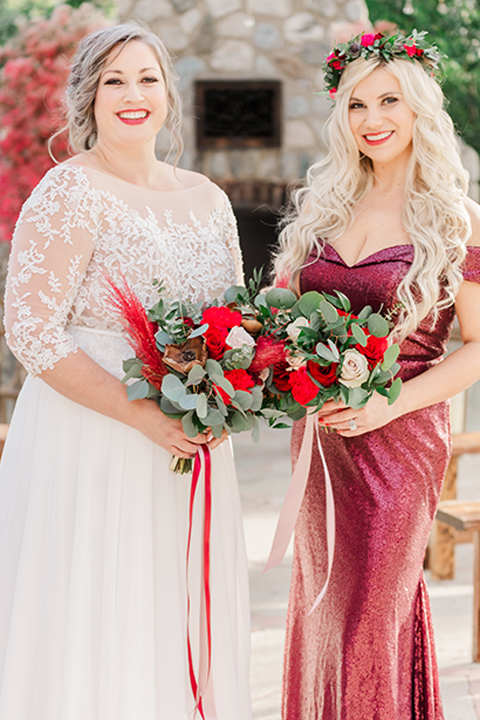 bride in a white and ivory gown with a natural waist and lace long sleeves and the bridesmaid in a red velvet long gown and a floral headpiece