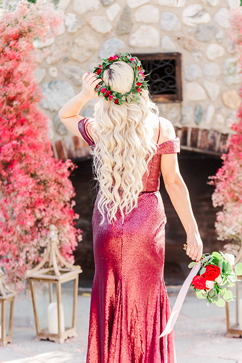 bridesmaid in a red velvet long gown and a floral headpiece