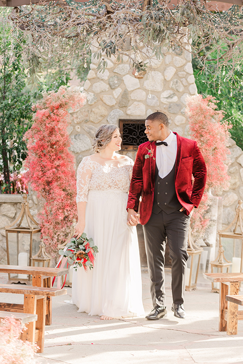 bride in a white and ivory gown with a natural waist and lace long sleeves, the groom in a burgundy velvet tuxedo with a black bow tie