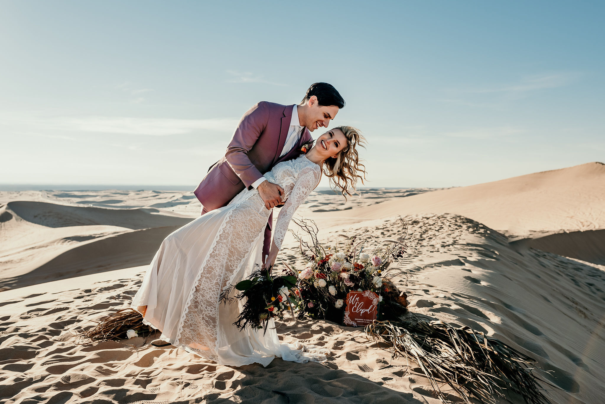 A bride and groom posing for photos in the desert